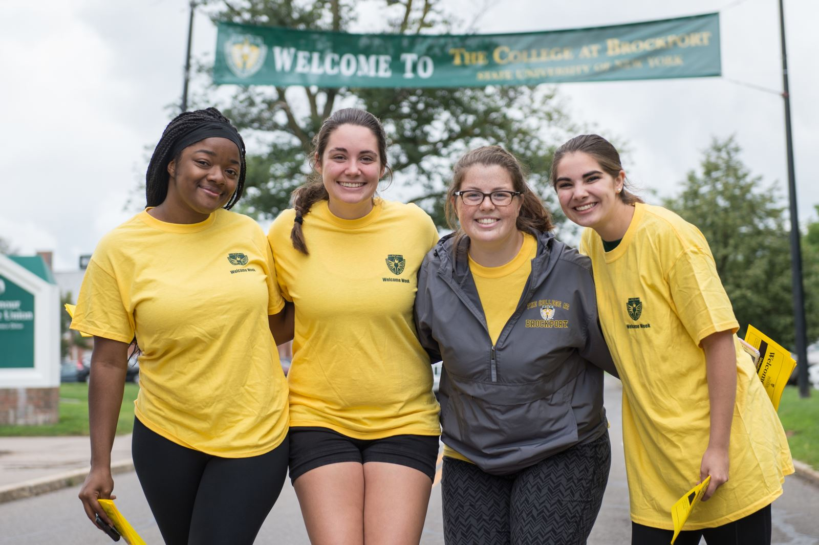 four smiling female students, with a Welcome to Brockport banner behind them.